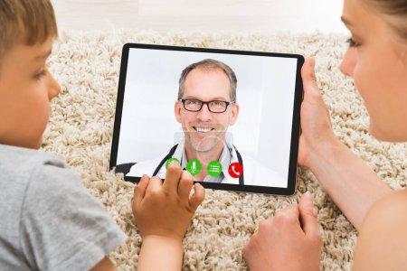 Photo pour Femme avec enfant dans la visioconférence en ligne avec le médecin - image libre de droit