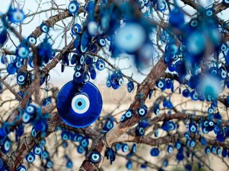 Photo pour Les branches du vieil arbre décorées avec les amulettes en forme d'œil - Nazars, en verre bleu et censé protéger contre le mauvais œil dans le parc national de Goreme, en Cappadoce, Turquie . - image libre de droit