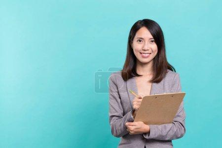 Business secretary taking note on clipboard