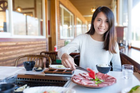 Woman having barbecue meat in Japanese restaurant