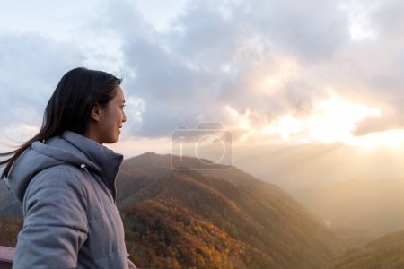 Photo for Woman looking at sunset on mountain - Royalty Free Image