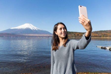 Woman taking photo with Mount Fuji
