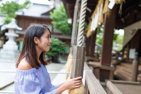 Young woman holding the rope in Japanese temple