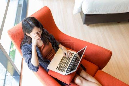 Woman feeling eye pain when using laptop computer