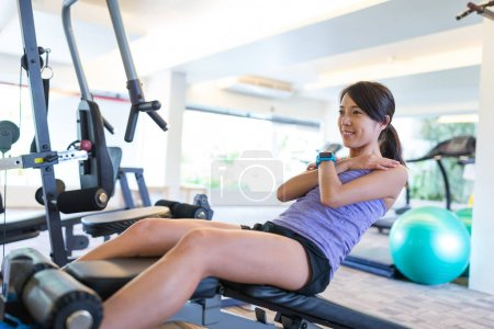 Woman doing sit up in gym