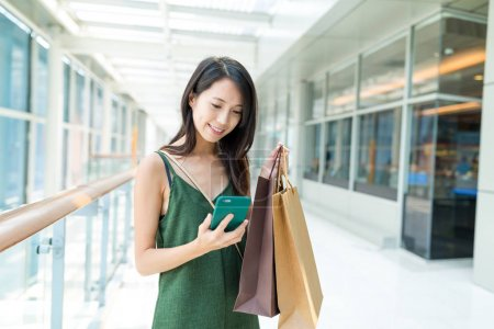 Woman holding shopping bags and using mobile phone