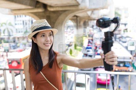 Woman taking selfie movie by video stabilizer