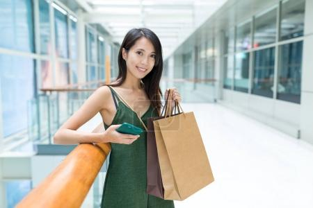 Woman holding shopping bags and cellphone