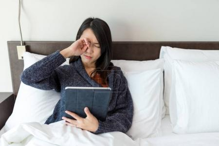 Woman feeling tired when using digital tablet