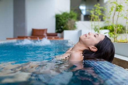 Woman relaxing in jacuzzi pool