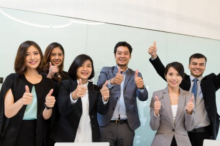 businesspeople showing thumb up in meeting room