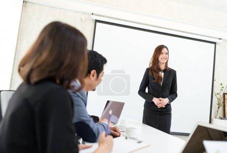 Femme d'affaires présente son projet à l'intérieur de salle de réunion