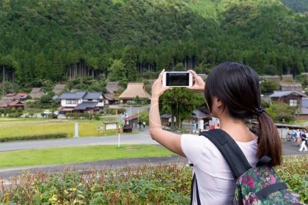 Woman taking photo on cellphone in Miyama