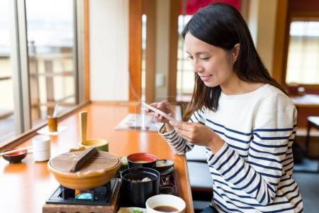 Photo pour Femme prenant des photos sur son repas au restaurant japonais - image libre de droit
