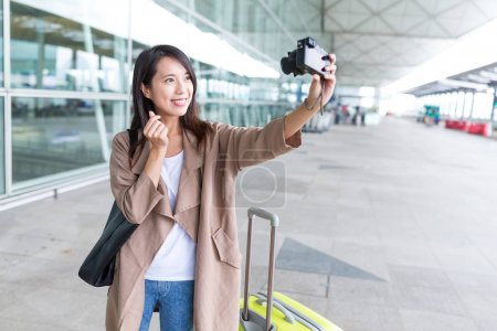 Woman taking selfie by camera in airport