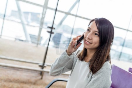 Woman talking on mobile phone in airport