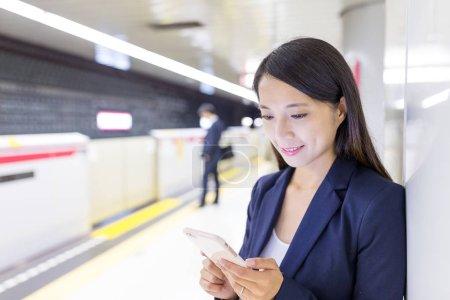 Photo pour Femme d'affaires travaillant sur téléphone portable dans la plate-forme du train - image libre de droit