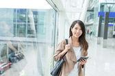 "Постер, картина, фотообои ""Woman holding cellphone and passport in airport"""