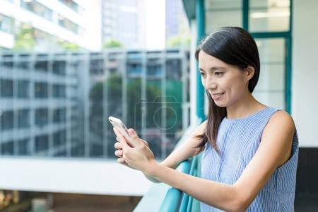 Woman using cellphone in office