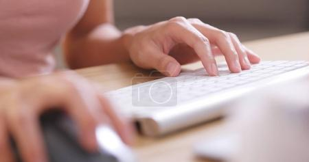 Hands typing on computer keyboard and using mouse in office