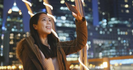 Woman using mobile phone for taking photo in the beautiful city background at night