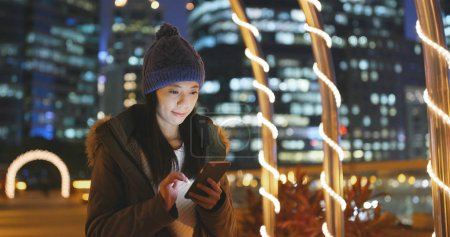 Woman using smartphone in the city at night, surf online on smartphone with urban city background, woman wearing winter jacket