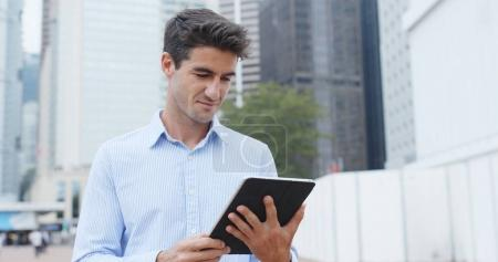 Businessman holding tablet computer in city