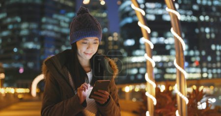 Woman using mobile phone in the city of Hong Kong, woman wearing winter jacket with building city background