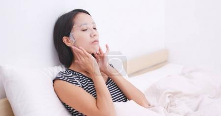 Woman apply paper mask on bed