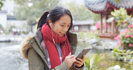 Woman listen to earphone and surf the internet on mobile phone in china