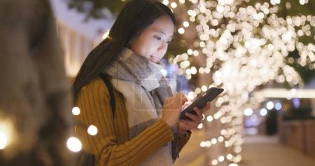 Woman using mobile phone at outdoor with light decoration