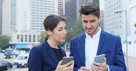 Photo pour Gens d'affaires à l'aide de smartphone ensemble, d'autres montrant sur smartphone à l'extérieur du Bureau - image libre de droit