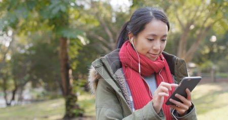Woman enjoy listening the song on mobile phone with wearing the earphone at chinese garden