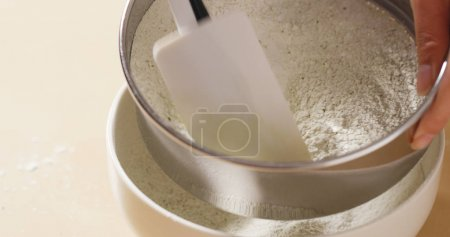 Stirring flour through sieve