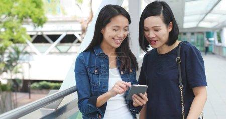Photo pour Amis utilisant le téléphone portable ensemble à l'extérieur - image libre de droit