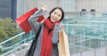 Woman using mobile phone and holding shopping bags