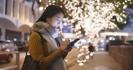 Woman watching on smartphone at night