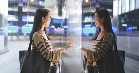 Photo for Woman choosing product inside shop window in the city at night with window reflection - Royalty Free Image