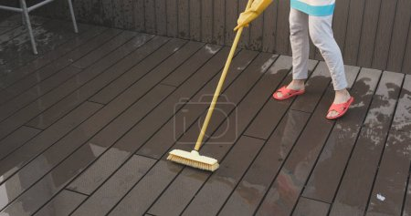 Woman brushing on the floor with water and detergent