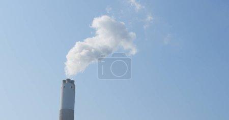 Chimney and smoke over blue sky