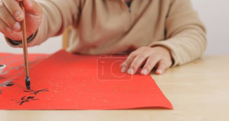 Elderly man writing Chinese calligraphy on red paper