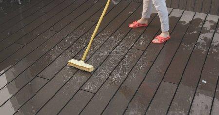 Woman splashing water and brushing on floor