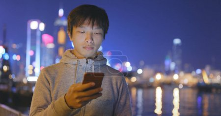 Young Man using smartphone in city at night