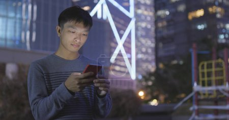 Man using smartphone in the city at night
