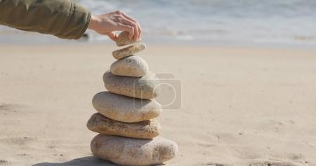 Hand putting the pebble stone on balance zen stock