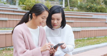 Friends using cellphone together at outdoor