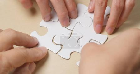 Hand put the piece of jigsaw puzzle, teamwork concept
