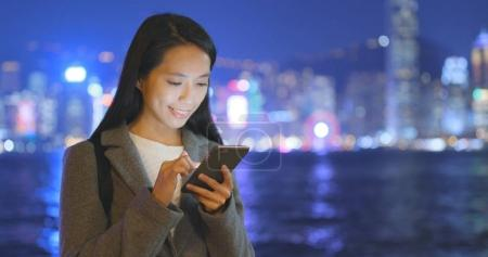 Businesswoman using cellphone in Hong Kong city at night