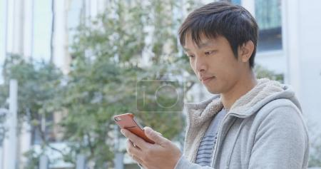 Asian Man using mobile phone in city