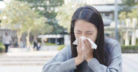 Asian Woman sneezing at outdoor